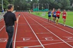Rainer Dohrmann (li.) sagte für die Läufer des 3000m-Laufes die jeweiligen Zwischenzeiten an, wobei er für die beiden Aktiven in den blauen Hemden der LG Kreis Verden diesen Service auch in englischer Sprache lieferte.