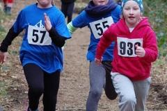 Szene aus dem Lauf der weiblichen Kinder über 700m, in der Stina Mittmann (Nr. 936, LAV Zeven, W08) von den beiden um ein Jahr älteren Läuferinnen Lena Kimpel (Nr. 55) und Frederike Neumann (Nr. 57) vom TuS Rotenburg verfolgt wird.