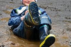 Dieser junge Zuschauer testete am Rand der Wettkämpfe die Tiefe der Pfützen und die Dichtigkeit seiner Kleidung. Seine Mutter nahm es mit Humor, da Kleidung zum Wechseln im Auto lag.