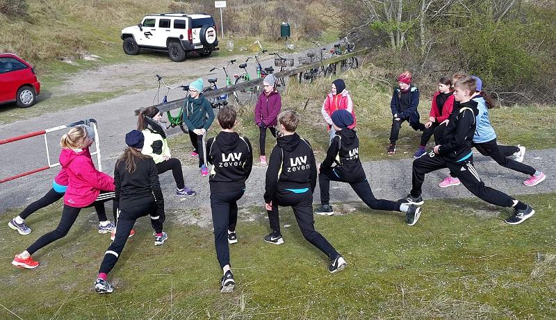 Die Leichtathletinnen und Leichtathleten bei Dehnübungen.