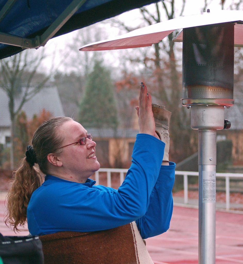 Auch diese Hammerwerferin nutzte bei den Winterwurf-Meisterschaften die aufgestellten Heizgeräte um sich zwischenzeitlich aufzuwärmen.