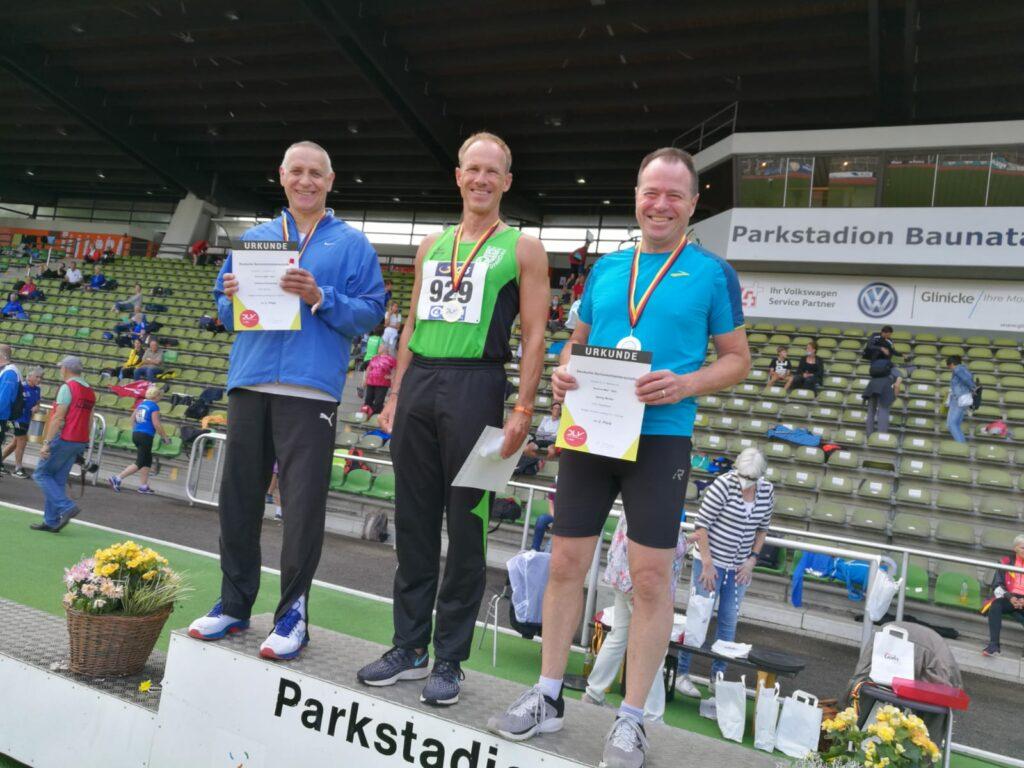 : Siegerehrung des Wettbewerbs über die 100m der M60 mit Czeslaw Pradzynski (li.).